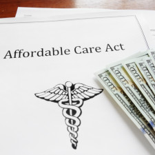 Affordable Care Act insurance papers with cash