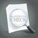 Reviewing a background check report with a magnifying glass.