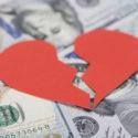 Closeup of red broken heart on dollar bills