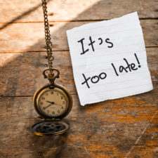 Ti's too late message on Vintage pocket watch on chain and torn paper on wooden background